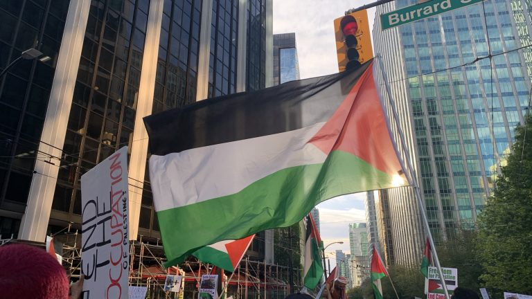 The flag of Palestine, consisting of black, white and green stripes bordered by a red triangle, is flown during a protest down Burrard Street in Vancouver. Signs carried by protestors read 'end the occupation'